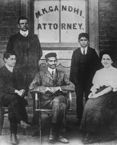 Mahatma Gandhi (Mohandas Karamchand Gandhi, 1869 - 1948) when he was practising as an attorney in South Africa. He is seated in front of a window bearing his name, on the left is H S L Polak then his clerk. The woman is Miss Schlesin, a Russian.   (Photo by Keystone/Getty Images)