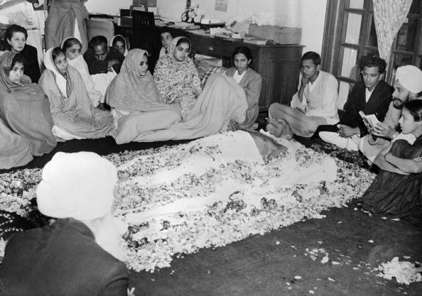 A Sikh priest reciting the scripts from the Gurugranth Saheb, while the body of Indian statesman and advocate of non-violence, Mahatma Gandhi (Mohandas Karamchand Gandhi), lies in state, covered with a Khadar sheet. (Photo by Fox Photos/Getty Images)