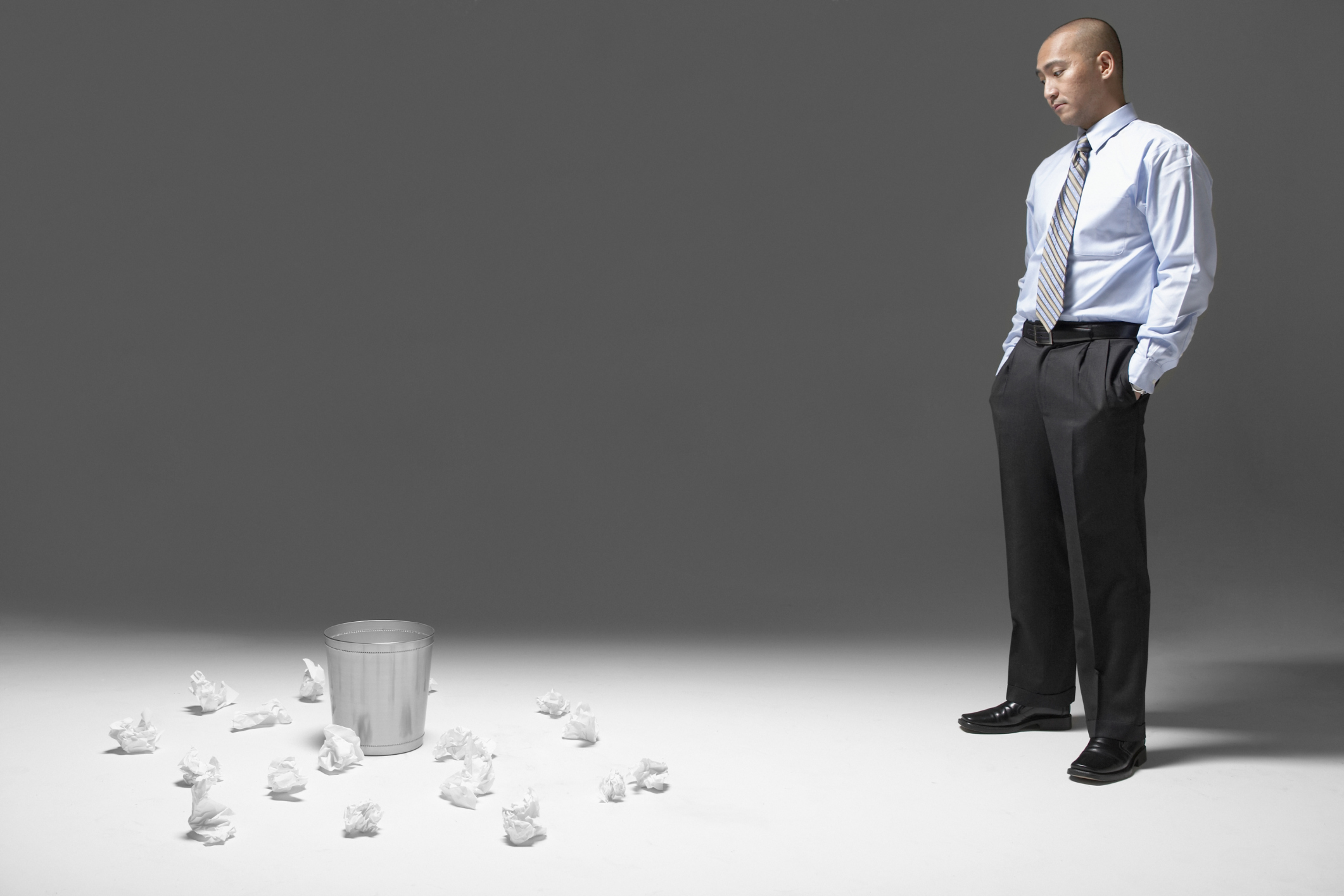 Businessman with hands in pockets, looking at waste paper basket
